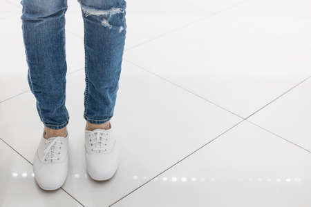 Feet in jeans and white sneakers stand on the floor of white tiles in the store. The girl measures the new shoes, walks on the floor, trying to understand, comfortable or not. Reklamní fotografie