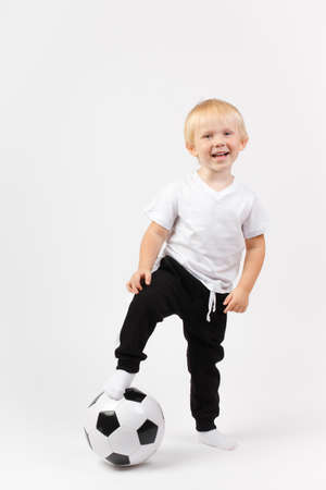 A blond European boy stands with one foot on the ball and laughs. Concept for advertising sports or childrens clothing, football.