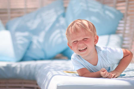 Handsome blond toddler boy laughing. Happy childhood concept with place for text.