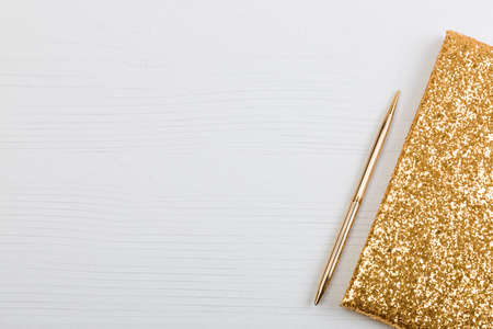 Golden sparkling notebook for recording closeup and a pen lying on a white table.