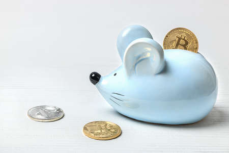 Blue mouse piggy bank on a white background with bitcoin coins.