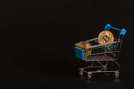 Gold bitcoin coins sparkle in a supermarket trolley on a black background.