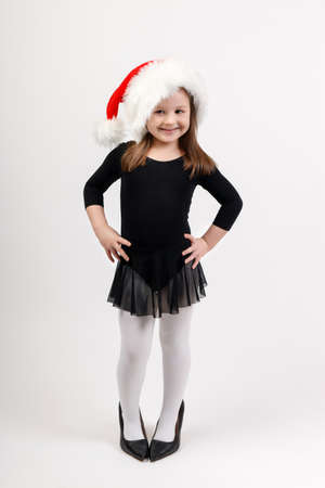 Little girl in ballerina costume and santa claus hat is standing and smiling. Concept for advertisements about ballet and New Year and Christmas celebrations. Zdjęcie Seryjne