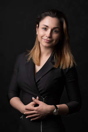 Beautiful business woman in formal suit dress smiling looking at camera on black background. Concept for corporate posts and articles, classic ads.