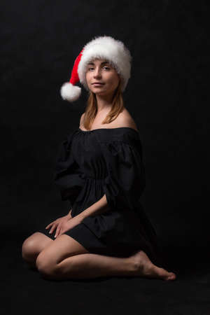 A girl in a black dress and Santa Claus hat is sitting on the floor on a dark background. Concept for illustrating different topics of articles.
