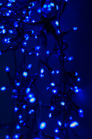 Christmas garland with blue lights on a dark background. For articles about the new year and holiday decorations and houses.