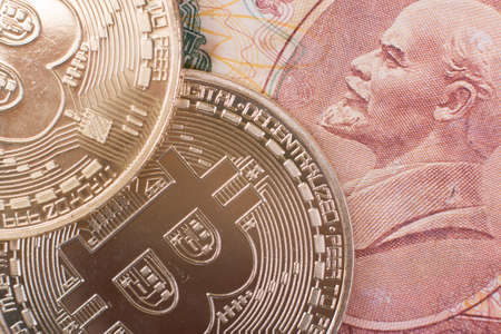 Two Bitcoin coins lie on top of Soviet paper money rubles with the symbol of the USSR Lenin. Concept for articles and posts about past and future money and political confrontation.