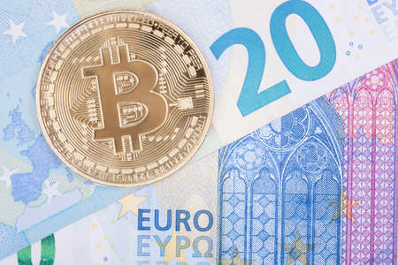 Bitcoin gold coin lies on paper euro, top view. For articles on the course of cryptocurrencies and ordinary money.