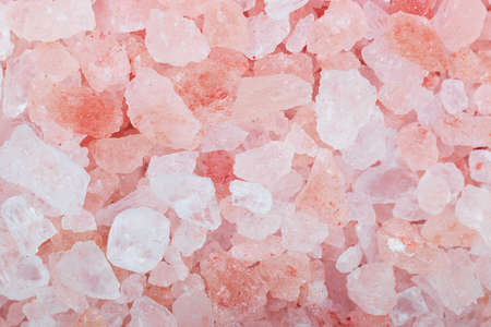 Grains of crystals of pink Himalayan salt, closeup shot on macro. Template for labels and packaging, texture for articles and posts about healthy and proper nutrition.