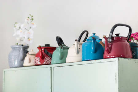 Old metal multi-colored teapots stand on a wooden cabinet. Collection for articles and posts.