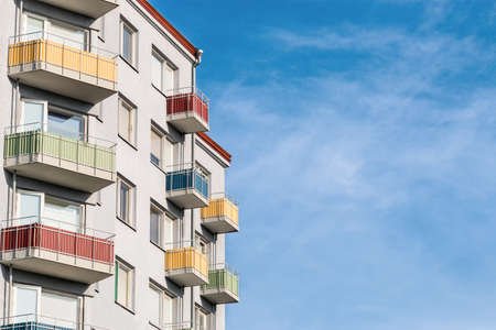 A light gray clean and tidy house building with colored balconies against a colorful blue sky. Concept for articles and posts on social networks about real estate and mortgage, with place for text. Zdjęcie Seryjne