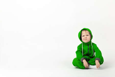 A displeased charismatic child in a bright green overalls sits on the floor and looks at the camera with doubt and contempt. Zdjęcie Seryjne