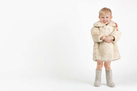 A child toddler in a light Soviet muton coat or sheepskin coat and gray felt boots is standing and looking at the camera on a white background with place for text.