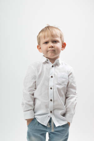 Portrait of a stylish and fashionable charismatic boy, frowning and serious in a white shirt on a light background.