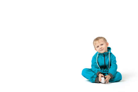 The baby blond-haired boy sits on the floor in a turquoise jumpsuit and smiles at the camera on a white background with place for text.