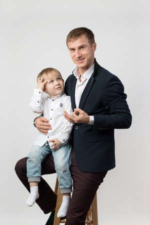 A child boy of 3 years old is sitting in the arms of his father, a young businessman at a photo shoot, a man is looking at the camera and is telling something. Zdjęcie Seryjne