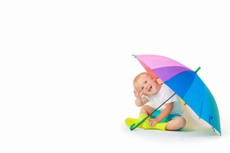 A blond child caucasian sits under a rainbow bright umbrella in rubber boots and waves his hand on a white background. Concept about puddles, security, bank account protection, with place for text. Zdjęcie Seryjne