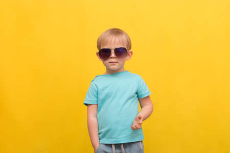 Child portrait of a 3 years old blond boy in a blue T-shirt and sunglasses on a bright yellow spring summer background with place for text. Attracting attention, juicy hat for articles and posts.