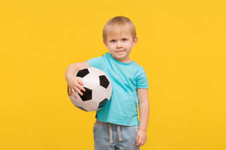 A blond boy stands with a soccer ball and looks at the camera with a challenge and anticipation. A child on a spring bright yellow background with place for text, an idea for articles about sports.