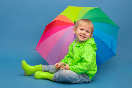 A caucasian child sits in a windbreaker jacket and rubber boots under an umbrella - a rainbow, on a blue background. Concept about weather and seasons, spring and autumn with puddles and rain. Zdjęcie Seryjne