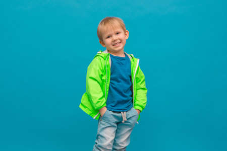 Happy blond boy child in a light green windbreaker raincoat laughing on a blue sea wave background. A concept about childhood, bad weather and rain, for advertising beautiful casual clothes.