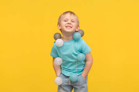 Happy blond boy child in a blue T-shirt laughs on a yellow background, and a garland hangs on his neck as a decoration. The concept of childhood and pranks, games and fun, celebration and joy.