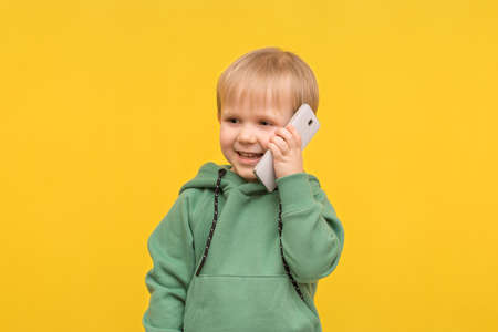 Child boy blond talking on the phone smartphone on a yellow spring background. Concept for articles about modern childhood, children's communication, the impact of technology on development. Zdjęcie Seryjne