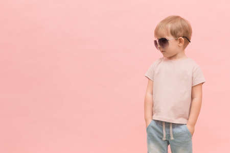A blond European-looking child boy stands in sunglasses and looks left on a pink background. Concept with place for text, for articles about models, castings and fashion shows.