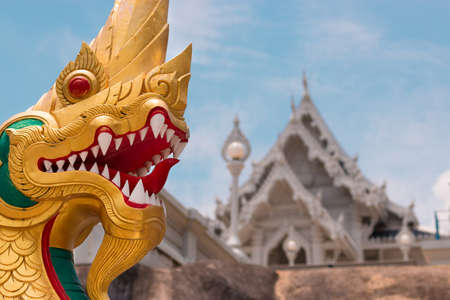 KRABI, THAILAND - APRIL 3, 2018: The head of a golden dragon against the white Buddhist temple Wat Kaew Korawaram, in the north of the country. Publikacyjne