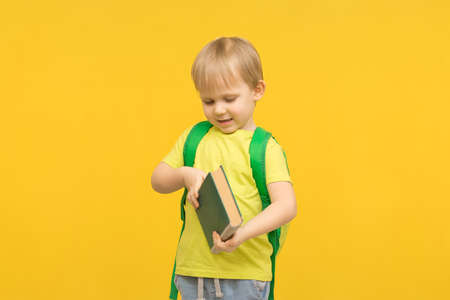 Child blond boy with a backpack opens a book on a yellow bright background. Concept for articles about study, reading, childhood and preschool children, kindergartens and classes.