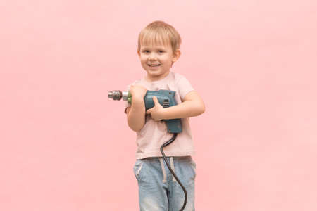 Happy boy stands and holds a real electric drill of blue color. For articles on appliances and tools, their ease of use and children's education.