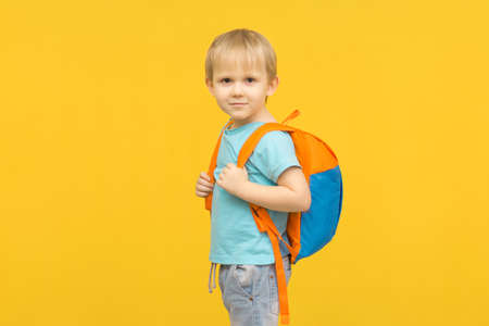 Joyful boy child stands with a backpack on his back and looks at the camera on a bright yellow background. Idea for travel articles and comfortable baby clothes.