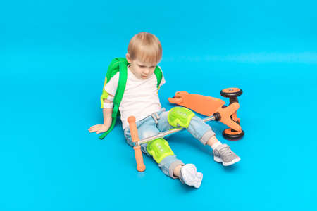 Child blond boy in protection on his knees and elbows with a backpack fell from a scooter on a bright blue background.