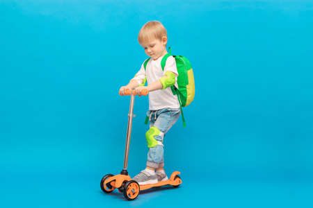 A blond-haired boy of 4 years old, a child with a backpack and in jeans with a white T-shirt rides on an orange scooter with light green protection on his elbows and knees. Security concept on azure.