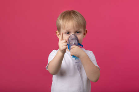 A blond child with an inhaler in his hand attached to his mouth points a finger at a plain pink background. Studio photography for medical topics of treatment, cough and coronavirus. Zdjęcie Seryjne