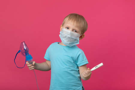 A blond child with an inhaler and a thermometer in his hand on a plain pink background. Studio photography for the treatment of temperature, cough and coronavirus, tonsillitis and colds, pneumonia.