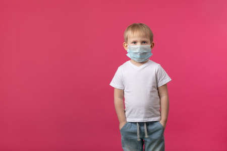 A blond European-looking child boy stands in a medical mask from a coronavirus and looks at the camera. Studio shot on a pink background with place for text for pandemic topics, protection and safety.