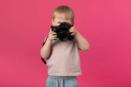 A kid boy of European appearance blond photographs with a camera. Close-up studio shot on a pink background for articles about recruiting for schools and courses, shooting training. Zdjęcie Seryjne