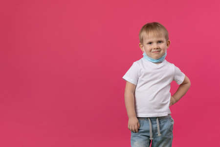 A blond boy child stands on a bright pink background, hand to side and looks mockingly and sarcastically at the camera, a mask is put on his face. Close-up studio shot concept with place for text. Zdjęcie Seryjne