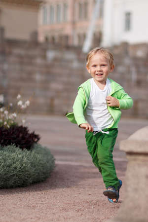 A blond child of European appearance in green clothes happy runs along the Senate Square in Helsinki in Finland. The idea of childhood, freedom and health.