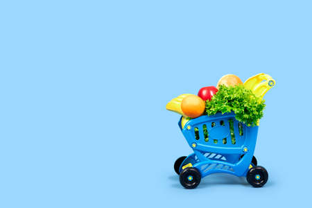 A grocery shopping cart full of salad, oranges, bananas, apples and bread. Close-up concept with place for text on a blue background. For articles, advertisements, and shopping and basket posts. Zdjęcie Seryjne