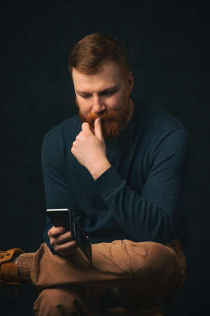 A young guy with a red beard of Irish appearance sits and thinks while reading a phone on a dark background. The concept of the impact of social networks, gadgets and smartphones on the life people.