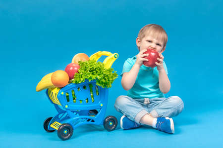 A hungry blond child sits near a supermarket basket full of food carts and bites a huge red apple. The concept of food delivery and healthy eating fruits and vegetables. Studio shot for advertising.