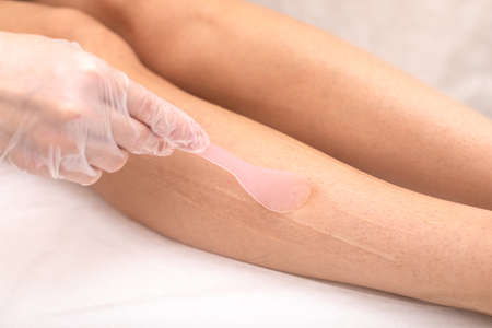 Laser hair removal on legs, hair removal by radiation. Spread a cooling cream on the skin before the procedure. Hands in gloves, closeup studio shot. Concept for articles about beauty services.