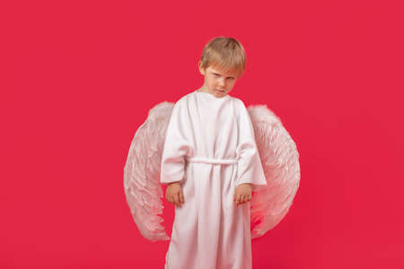 Angel with large wings sad resentment anger look into camera. Studio shot portrait on red isolated background. Valentine's day concept on February 14, lover, loneliness.