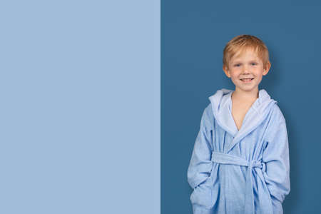Mockup template caucasian child laugh smile in bathrobe for sauna. Advertising concept for children clothing store and spa, swimming pool. Studio shot with blue bar with copy space text.