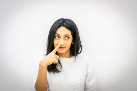 Close up face of Young brunette caucasian woman having finger in her right nose nostrils and looking to the side in white background. Silly bored and relaxed person at work concept.