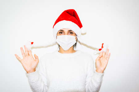 Young caucasian woman isolated in white background shows holding her white fake braids. Snowflake and Santa Claus concept.