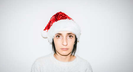 Close up of Unhappy caucasian woman face with christmas hat on in isolated white background. Dissapointment and sad xmas holidays. Imagens