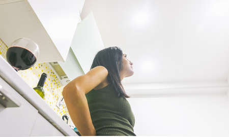 Low angle view of thoughtful woman leaning on kitchen table and looking up to the light. Concept of isolation at home during pandemic and depression